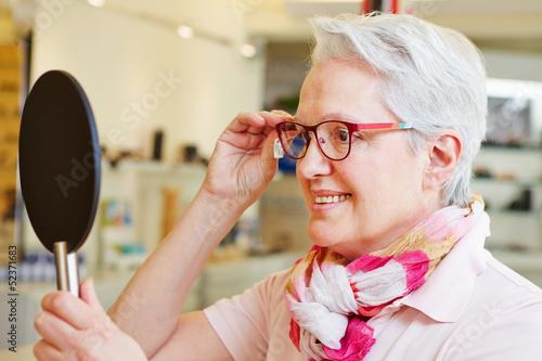 Seniorin mit Brille schaut in Spiegel