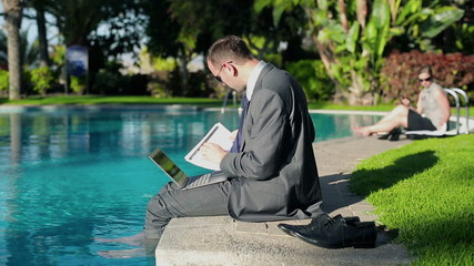 Businessman working with notebook and papers by swimming-pool