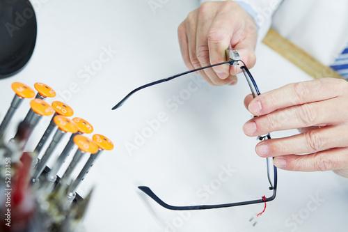 Fototapeta Hand eines Optikers repariert Brille