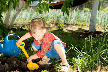 Young boy digging in the garden