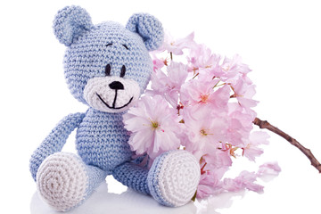 blue teddy bear stuffed animal with pink blossom.