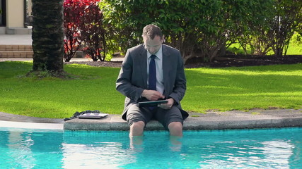 Businessman sitting by the poolside and working on tablet comput