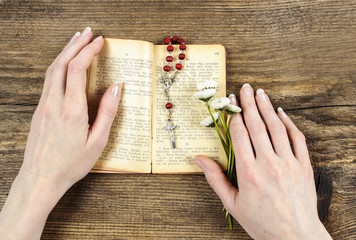 Hands holding the Bible and praying with a rosary