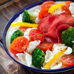 Gluten-free pasta with cherry tomatoes, broccoli and bresaola
