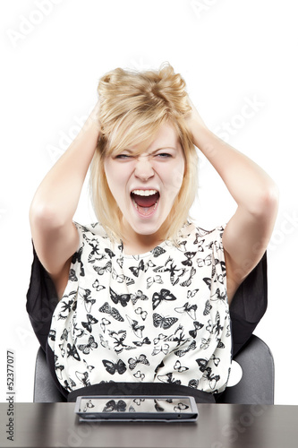 Blonde woman in business attire very angry and upset at desk
