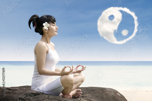 Beautiful girl exercise yoga  at beach under ying yang cloud