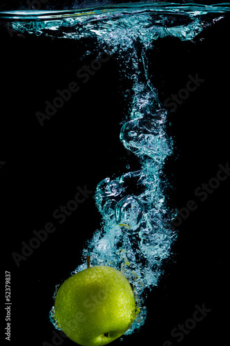 Green apple and water splashing