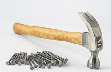 metal-headed hammer  and group nails isolated on white