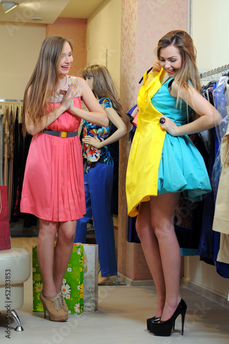 two smiling woman shopping in retail store