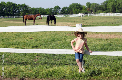 happy little girl with cowboy hat on ranch