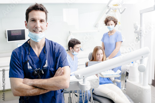 A portrait of a dentist with his team working in the background - 52386060