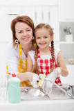 Woman and little girl washing dishes in the kitchen