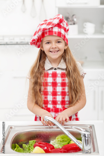 Little chef washing vegetables