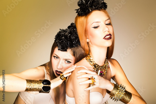 two beautiful girls wearing make-up and gold accessories