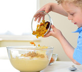 Child pouring raisins into a bowl