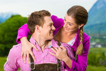 Paar in Tracht auf Wiese vor Bergpanorama