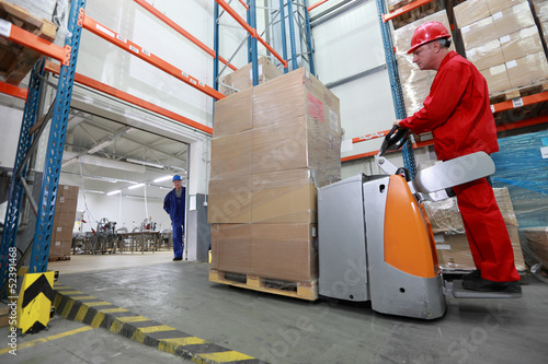 forklift loader with cardboard freight moving in storehouse