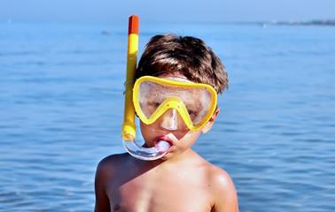 Bambino abbronzato indossa la maschera da sub e boccaglio