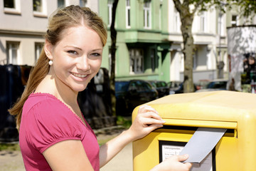 Junge Frau vor Briefkasten