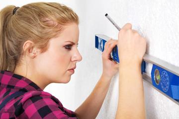 Junge Frau mit Wasserwaage zeichnet an Wand