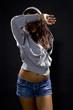 Latina hip hop dancer wearing a hoodie over a black background.