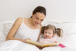 Child reading a book with her mother
