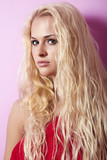 Beautiful blond woman with long hair. pink background