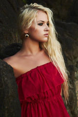 Beautiful blond woman near a rock
