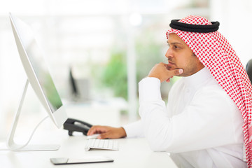 middle eastern businessman looking on a computer screen