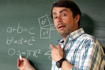 Lehrer mit Losüng an Tafel dreht sich zu Schülern