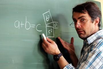 Lehrer mit Brille an Tafel erklärt Mathematikformel