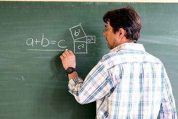 Lehrer schreibt Formel an die Tafel