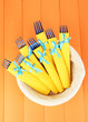 Blue plastic forks wrapped in yellow paper napkins, in basket,