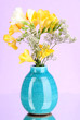 Beautiful bouquet of freesia in vase on purple background