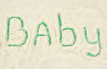 Word baby making with powdered milk on green background
