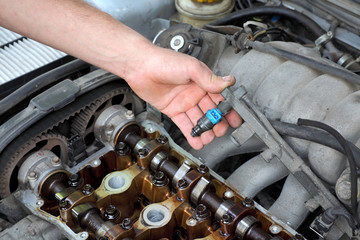Mechanic fixing fuel injector, two camshaft car engine