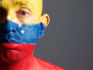 Man face painted with venezuelan flag, sad expression.