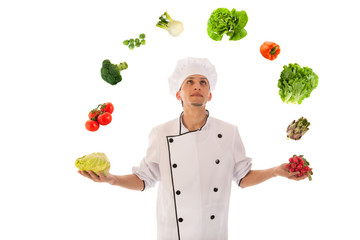 Cook juggling with fresh vegetables