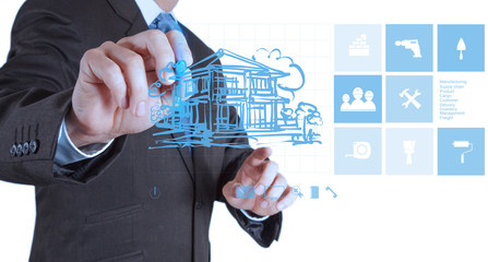 businessman hand drawing house with modern computer interface