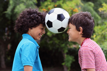 Two young boys playng with a soccer ball - close view