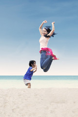 Asian mother jumping with daughter at beach