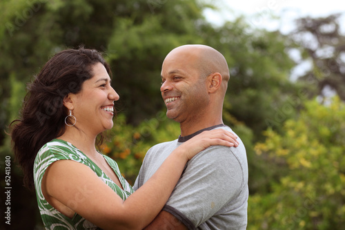 A happy mixed race couple relax outside - with copy space