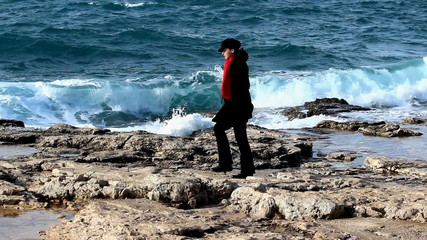 Woman with red scarf walking by the sea.