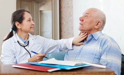 Doctor touching  neck of  senior man