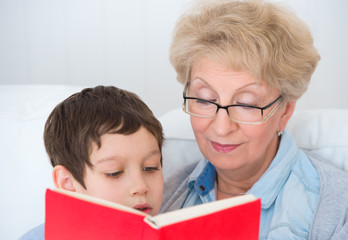 Grandmother and little boy reading book happy together at home