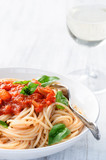 Spaghetti with red tomato sauce and basil garnish