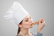 Woman in chef's hat tasting sauce with a wooden spoon
