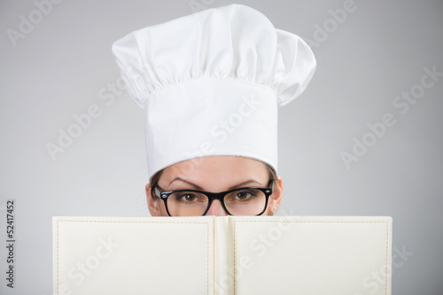 Woman in chef's hat looking at camera over the cookbook