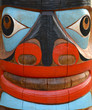 Detail Of A Brightly Painted Face On A Totem Pole