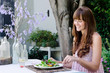 Woman eating salad, alfresco dining